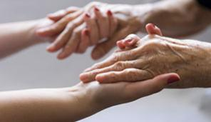 Young person's hands holding elderly hands