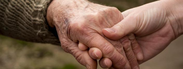 Younger hand holding elderly hand